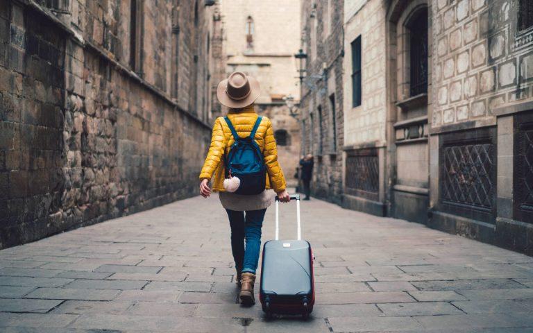 Chica con maleta en mano viajando sola