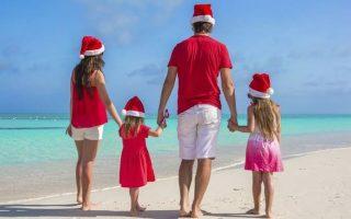 Familia con gorros navideños en la playa
